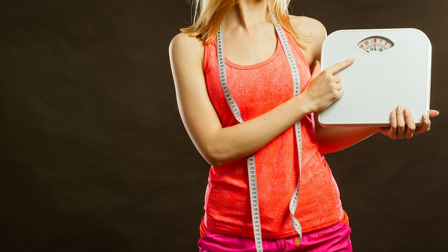 bigstock-Gym-Woman-Holding-Weight-Scale-98049386.jpg